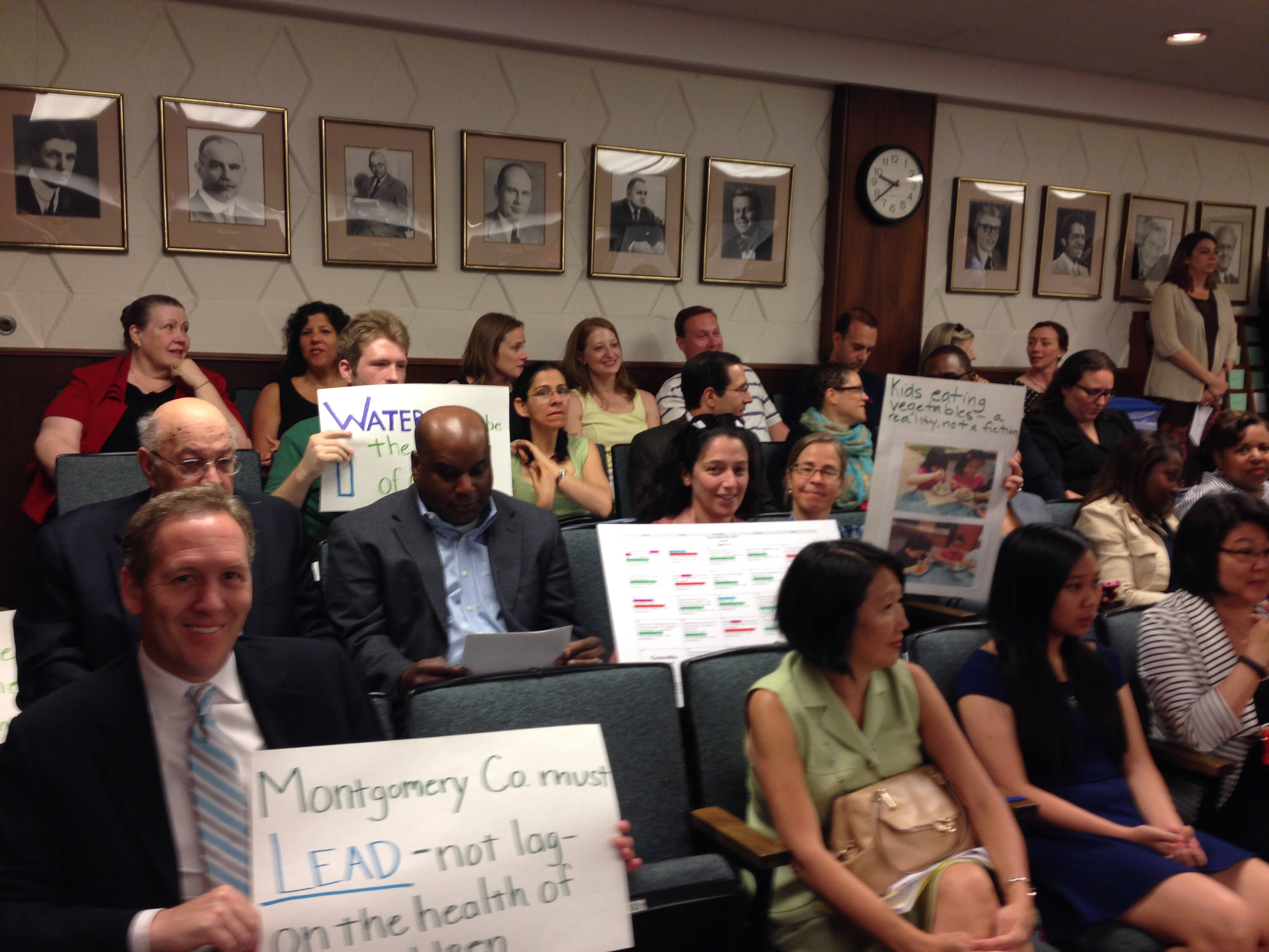 Parents holding signs at BOE meeting